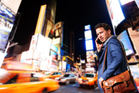 Young urban professional business man talking on smart phone onTimes Square, Manhattan, New York City. Young hip male businessman in casual suit in at night outdoors.