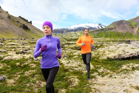 cross country: Running sport. Runners on cross country trail outdoors working out for marathon. Fit young fitness model man and asian woman training together outside in mountain nature.