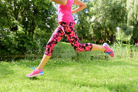 Female runner running shoes and legs in city park. Woman jogging wearing floral capris leggings compression tights and pink running shoes. Stock Photo