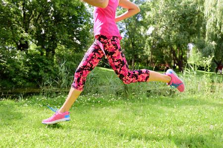 Weiblicher Läufer Laufschuhe und Beine im Stadtpark. Frau Joggen tragen Blumencaprihosen Leggins Kompressionsstrumpfhose und rosa Laufschuhe.