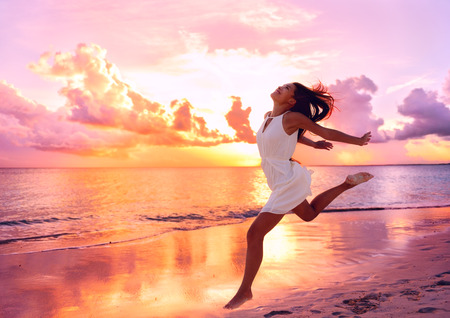Gelukkig prachtige vrije vrouw die op het strand bij zonsondergang springen speelse plezier in een serene prachtige zonsondergang op de oceaan. Aspirational gelukkig leven met mooie jonge dame geniet van de vrijheid. Stockfoto