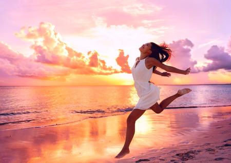 Glückliche schöne freie Frau am Strand bei Sonnenuntergang springt spielerisch Spaß im ruhigen malerischen Sonnenuntergang am Meer. Aspirational glückliches Leben mit hübschen jungen Dame genießen die Freiheit.