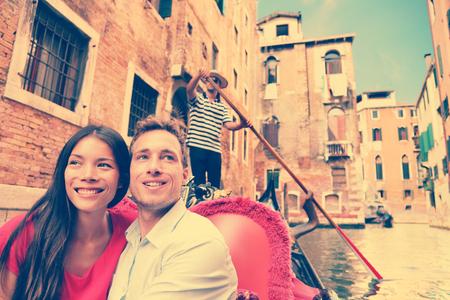 luna de miel: Par de viajes en Venecia en góndola paseo romance en barco hablando felices juntas de vacaciones vacaciones viaje. Pareja joven multirracial vela en canal veneciano en góndolas. Italia, Europa