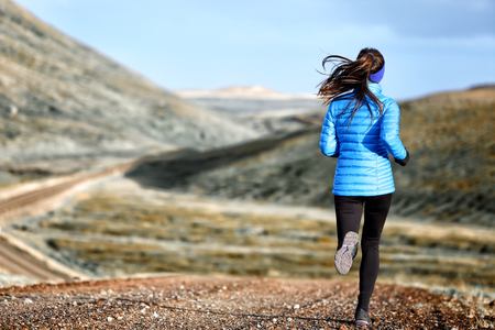 trails: Woman winter and autumn running in down jacket. Female running jogging on mountain trail in beautiful landscape.