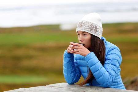 Frau im Freien Kaffee trinken aus Thermosschale sitzen draußen tragen warme Daunenjacke und stricken Hut. Hübsche junge Mischlinge Asiatisch Chinesisch kaukasischen Frau lebenden aktiven Lebensstil. Standard-Bild