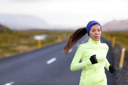 外秋と冬用防寒服で実行されている女性ランナー。女性ランナーの寒さ生活健康的なアクティブなライフ スタイルのトレーニングです。