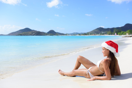 sun tanning: Christmas beach woman in santa hat and bikini on holidays travel vacation getaway relaxing on beautiful tropical beach with turquoise water in the Caribbean. Beautiful young female model sun tanning.