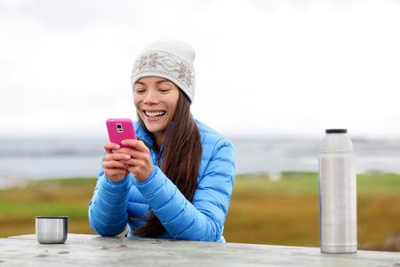 Frau im Freien mit Smartphone-App für Smartphone-Kaffee zu trinken aus Cup sitzen draußen tragen warme Daunenjacke. Hübsche junge Mischlinge Asiatisch Chinesisch kaukasischen Frau in aktiven Lebensstil.