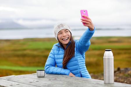 Frau im Freien mit Smartphone unter selfie Photo-App auf dem Smartphone, während draußen sitzen tragen warme Daunenjacke. Hübsche junge Mischlinge Asiatisch Chinesisch kaukasischen Frau in aktiven Lebensstil. Standard-Bild