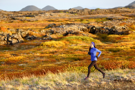 run: Woman trail runner running in mountain landscape. Female runner in warm winter and fall outfit jogging cross country outdoors in beautiful nature.