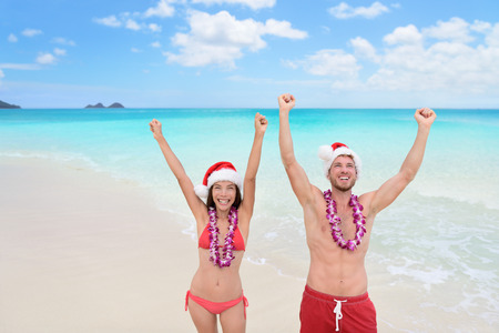 Happy Christmas holiday - multiracial joyful couple cheering arms up on Hawaii beach for their winter vacation during new year. Stock Photo