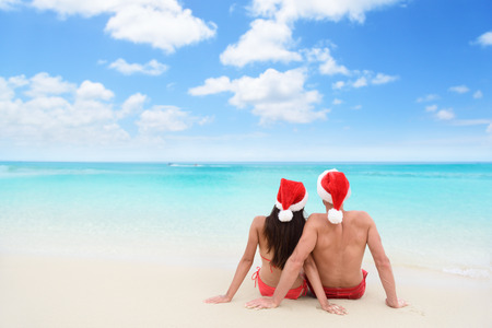 sun beach: Christmas couple in love lying down relaxing on white sand beach sun tanning in tropical travel destination during winter holidays. Back view of young adults wearing santa hat. Stock Photo