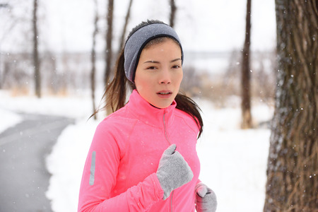 chinese adult: Woman running in cold weather wearing winter accessories, pink sweater, gloves and headband. Asian Chinese young adult doing her cardio exercises outside in a city park. Stock Photo