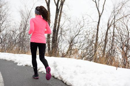 resfriado: Invierno activa en parque - corredora de la parte posterior de su ejercicio cardio llevaba chaqueta rosa, leggings activos y zapatillas en el camino de la ciudad.