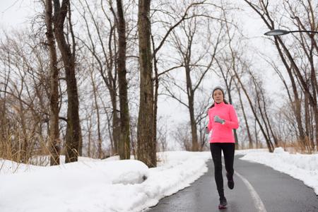 frio: Mujer trotar en el parque cubierto de nieve ciudad - la aptitud invierno. Atleta femenina ejercicio al aire libre en tiempo frío en pista forestal que lleva ropa deportiva. Rompevientos chaqueta de color rosa, medias de abrigo, zapatos para correr.