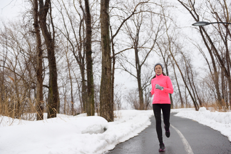 jogging: Woman jogging in snowy city park - winter fitness. Female athlete exercising outside in cold weather on forest path wearing activewear. Windbreaker pink jacket, warm tights, running shoes. Stock Photo