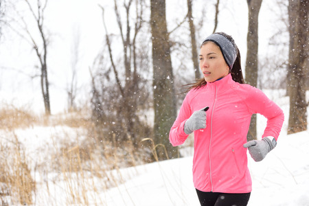 chinese adult: Winter jogging - young Asian Chinese adult woman runner running breathing cold air wearing pink jacket, headband and gloves doing a cardio workout.