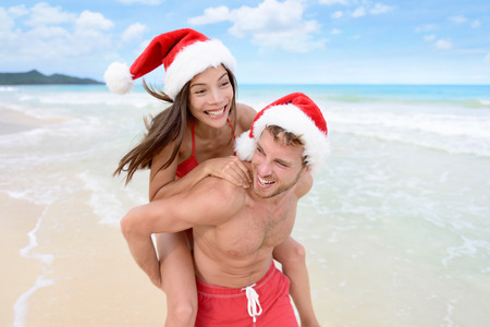 Christmas couple having fun on beach vacation doing piggyback. Laughing funny young friends playing on beach during winter holidays wearing santa hats. Multiracial people Stock Photo