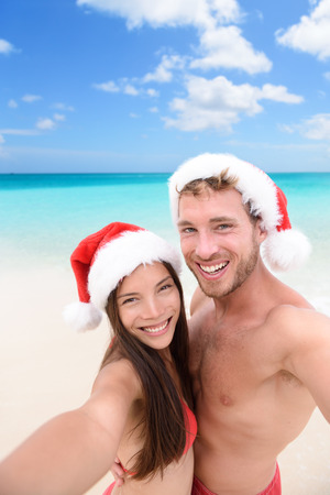 young asian couple: Happy couple on Christmas travel holidays taking selfie picture with smartphone wearing santa hat during their winter vacation. Young adult friends in swimsuit and bikini in front of the ocean.