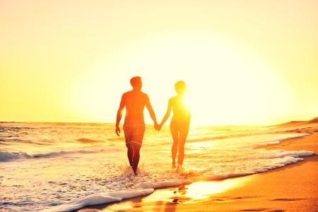 ロマンス: ロマンチックな新婚旅行恋日没歩行時手を繋いでいる夏のビーチのカップル旅行休暇の休日。認識できない女とビキニとショート パンツ カジュアル