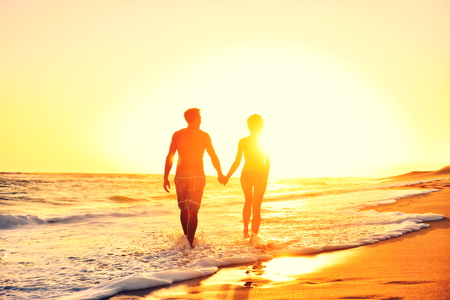 Summer beach couple romantic holding hands at sunset walking in love on honeymoon travel vacation holidays. Unrecognizable woman and man in happy romance wearing bikini and casual beachwear shorts. Banco de Imagens - 47346143