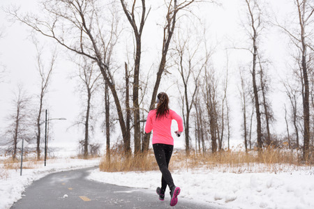 Woman runner running in winter snow - active lifestyle. Female athlete from the back jogging training her cardio on city park path outside in cold weather wearing leggings and coat. Stock Photo