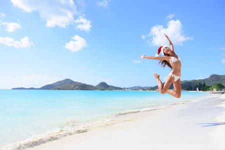 petite fille maillot de bain: Vacances Joyeux No�l - fille sautant de joie et de surprise parfaite plage de sable blanc pour des vacances d'hiver. Jeune femme portant no�l bras de chapeau soulev�es de bonheur pendant les vacances.