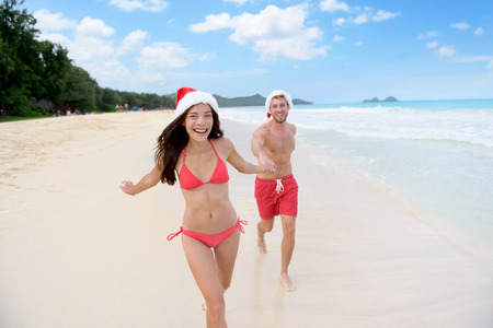 winter escape: Christmas couple happy relaxing on white sand beach running on sand in bikini and swimsuit. Asian woman and man holding hands running playing during travel holidays.