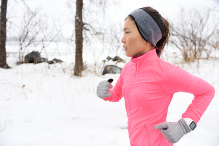 weather protection: Female runner trail running in cold snowing weather. Asian Chinese athlete woman training for marathon jogging outside in snow wearing activewear jacket, headband, and winter gloves.