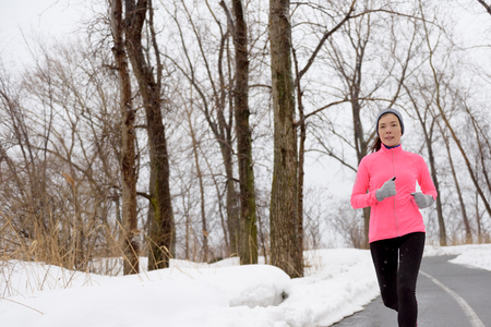 adult woman: Winter cardio exercise - woman jogging doing her workout outside. Young adult running in outdoor park with snowy forest background wearing cold weather gear. Stock Photo