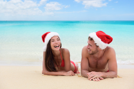 winter vacation: Christmas couple relaxing on beach winter vacation. Happy young adults friends or in love laughing on white sand in tropical travel destination for their new year holiday.