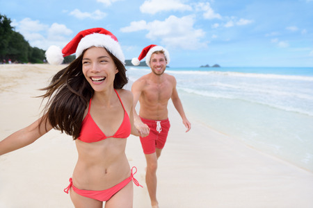 Happy Christmas couple having fun running on beach. Beautiful young Asian woman and Caucasian boyfriend holding hands playing on sand during winter travel holidays wearing santa hats. Stock Photo