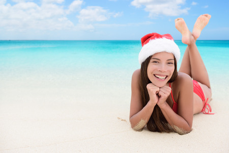 Christmas woman relaxing during winter beach holidays. Girl smiling at camera during travel vacation wearing a santa hat. Young mixed race adult in her 20s. Stock Photo