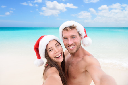 romantic beach: Christmas couple selfie picture on beach vacation. Happy young adults smiling at camera taking self-portrait wearing santa hats. Multiracial Caucasian and Asian people.