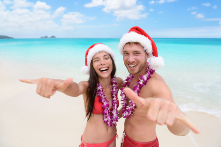 luna de miel: Vacaciones en Hawai Navidad - par hawaiano playa con sombrero de santa y hacer de bienvenida muestra del shaka feliz en la c�mara como gesto de bienvenida para las vacaciones de invierno.