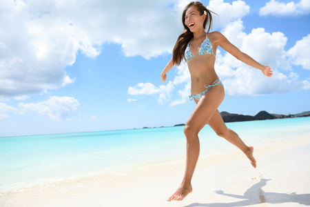 sexy asian woman: Happy beautiful woman running on the beach on travel vacation beach holidays in the Caribbean. Image full of aspiration and joy with multicultural Caucasian  Asian Chinese bikini model having fun. Stock Photo