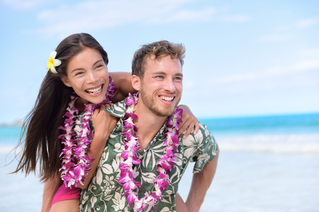 hawaiian lei: Happy beach couple having fun piggybacking and laughing on Hawaii travel holiday. Beautiful Asian mixed race woman abd Caucasian boyfriend wearing traditional Hawaiian lei on Oahu, Hawaii, USA.