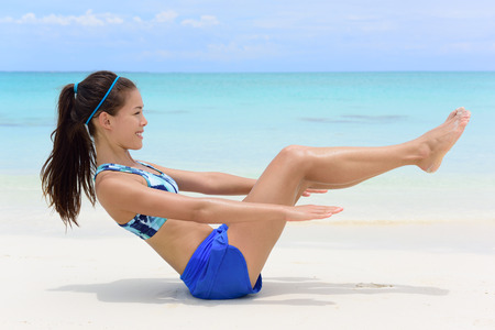 body toning: Fitness woman on white sand beach and turquoise ocean background exercising abs with sit-ups workout. Young female athlete doing ab toning exercises with v-up crunches as basic core body poses.