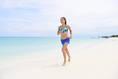 conscious: Jogging on beach - healthy fitness woman lifestyle. Young Asian woman portrait of a runner running barefoot in activewear in tropical white sand living a health conscious lifestyle.