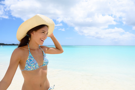 seaside resort: Woman in hat on the beach. Girl having fun laughing full of joy and aspiration on pristine Caribbean beach with turquoise water and white sand. Happy Eurasian Chinese  Caucasian bikini model.