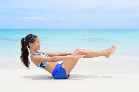 woman sitting on floor: Fitness woman on beach with toned in shape body body doing v-up crunch ab toning exercise workout as part of an active lifestyle for weight loss.