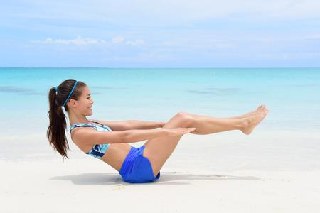 haciendo ejercicio: Mujer de la aptitud en la playa con tonificado cuerpo en cuerpo de la forma que hace crujido v-up ab entrenamiento del ejercicio de tonificaci�n como parte de un estilo de vida activo para la p�rdida de peso.