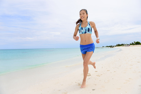 female athlete: Asian runner woman running on beach living healthy lifestyle. Young adult female athlete training her cardio doing morning jogging barefoot in Caribbean summer destination.