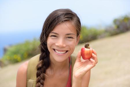 자연의 신선한 캐슈 너트 사과 과일을 보여주는 여자. 아시아 중국 여자 세로 미소 캐슈 너트에서 온 열대 나무에서 갓 사과 과일을 들고. 카리브해 음 스톡 콘텐츠