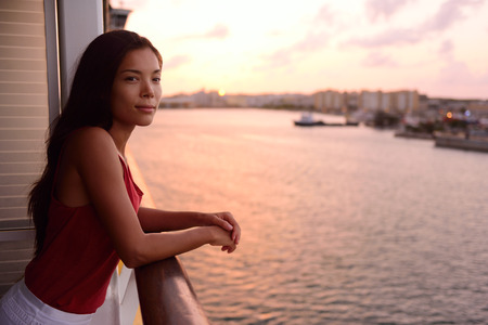luxury lifestyle: Cruise ship vacation woman enjoying balcony at sea with beautiful sunset on travel at sea. Relaxed woman enjoying private balcony in stateroom. Asian Chinese  Caucasian woman in dress on cruise liner.