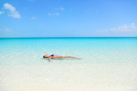 静かな青い水の中日光浴を楽しんでリラックスした海で泳いでいる女性。セクシーな女性大人の海の瞑想をフローティングします。