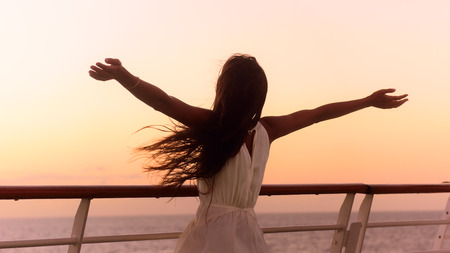 Cruise ship vacation woman enjoying sunset on travel at sea. Free happy woman looking at ocean in happy freedom pose with arms out. Woman in dress on luxury cruise liner boat.