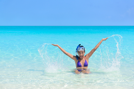 asian bikini: Beach holiday woman playing in the ocean. Asian young adult wearing a snorkel scuba mask having fun splashing water with arms up and swimming in vacation resort travel destination. Stock Photo
