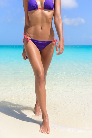Mujer atractiva del cuerpo de bikini curtida en vacaciones en la playa. Detalle de las piernas y la parte inferior del cuerpo en traje de baño de color púrpura de saludable y en forma hermosa chica caminando fuera de la natación en el océano.