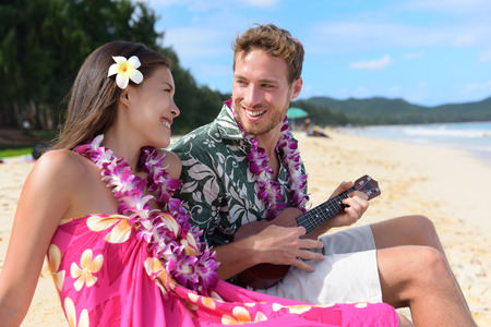 instruments: Man on beach playing ukulele instrument on Hawaii with having fun. Young couple, woman and man in love on beach vacations in Hawaiian clothing wearing Aloha shirt dress and flower lei.